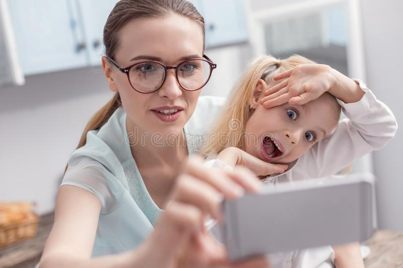 Attractive beautiful girl and woman saving moments. Free time. Charming young single mom putting on glasses while holding phone and daughter opening mouth stock photos