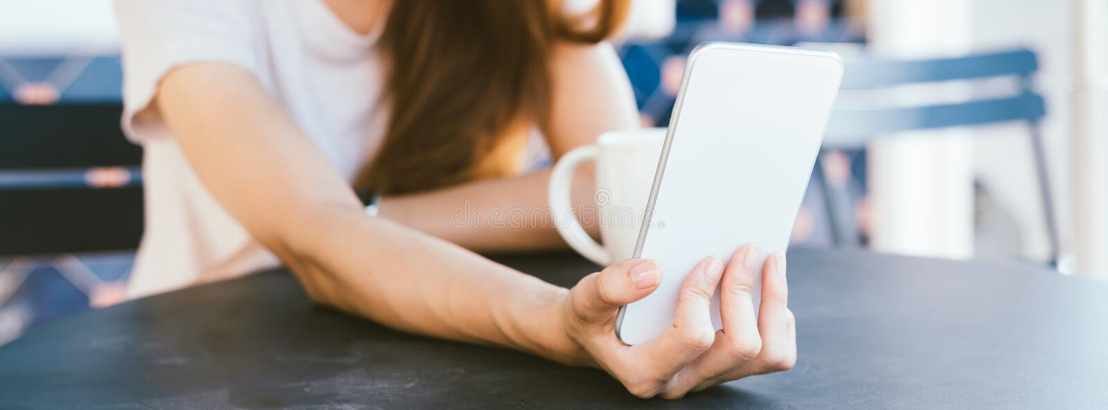Attractive beautiful happy young Asian woman taking a selfie using a smart phone at cafe. stock image