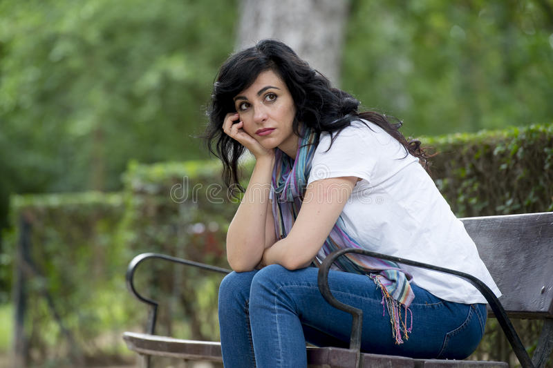 Attractive beautiful latin woman feeling sad and depressed. Attractive beautiful latin woman sitting on a park bench feeling sad and depressed in a park outside stock images