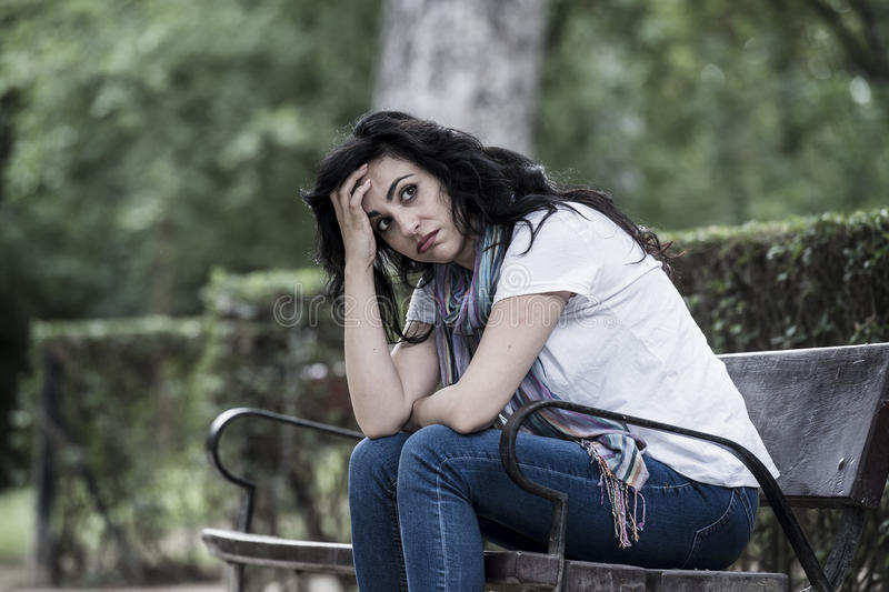 Attractive beautiful latin woman feeling sad and depressed. Attractive beautiful latin woman sitting on a park bench feeling sad and depressed in a park outside royalty free stock photography