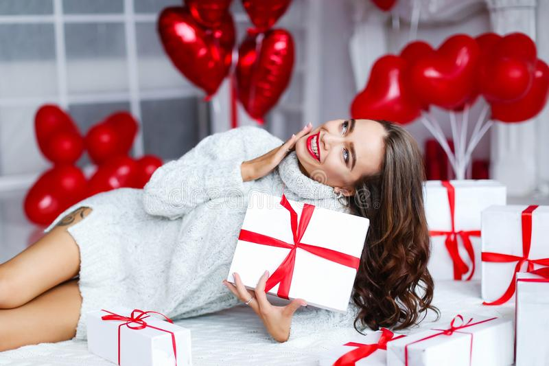Attractive beautiful and sexy woman with perfect smile and teeth. With makeup at birthday or valentines day holding gift stock photo