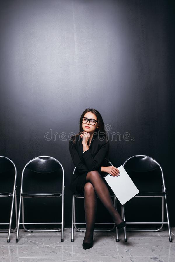 Attractive beautiful suit female student holding meeting file sitting on chair and looking at empty area thinking work planning fe royalty free stock image
