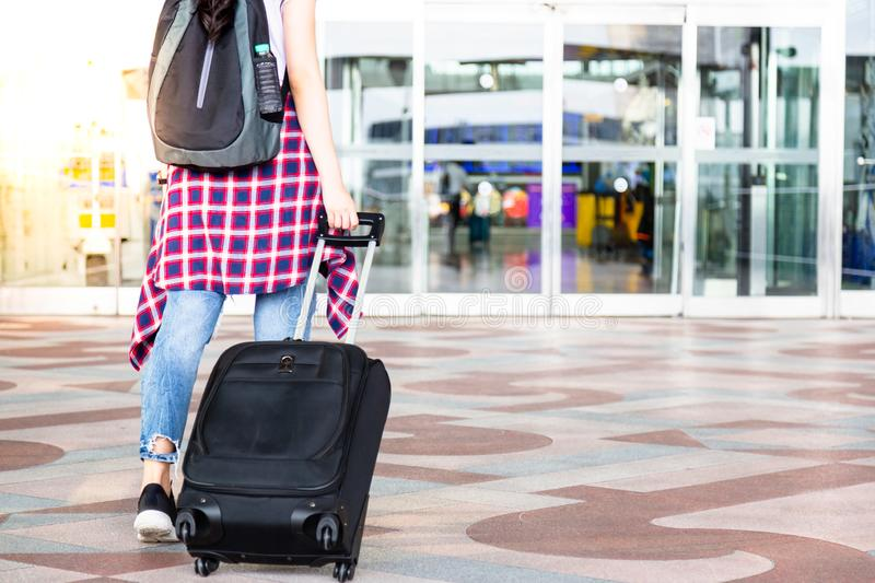 Attractive beautiful traveler woman is waking to airport and dragging suitcases, carrying backpack in front of gateway. Charming stock photos