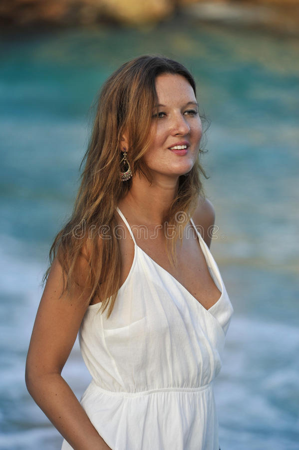 Attractive and beautiful woman enjoying vacation summer holidays at Spain coast village walking on beach stock photography