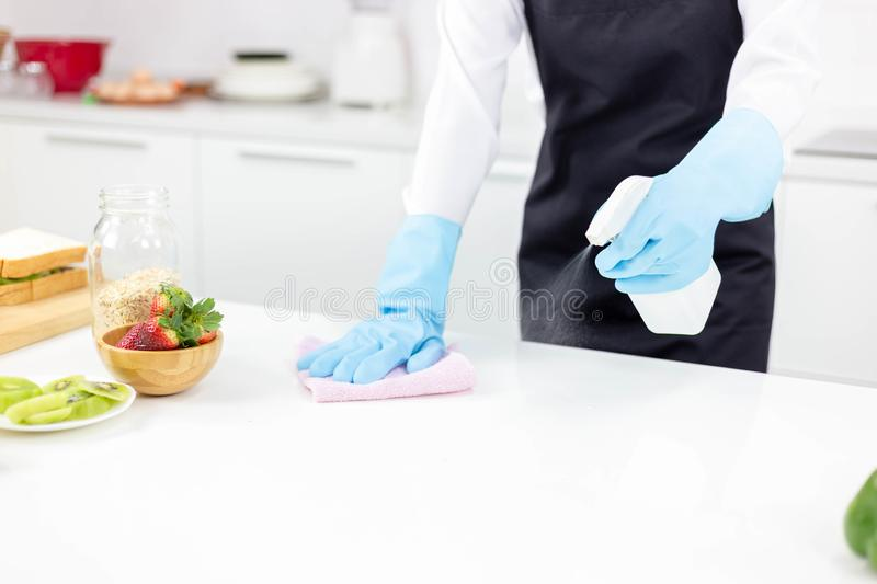 Attractive beautiful woman or housewife is wiping, cleaning and royalty free stock photo