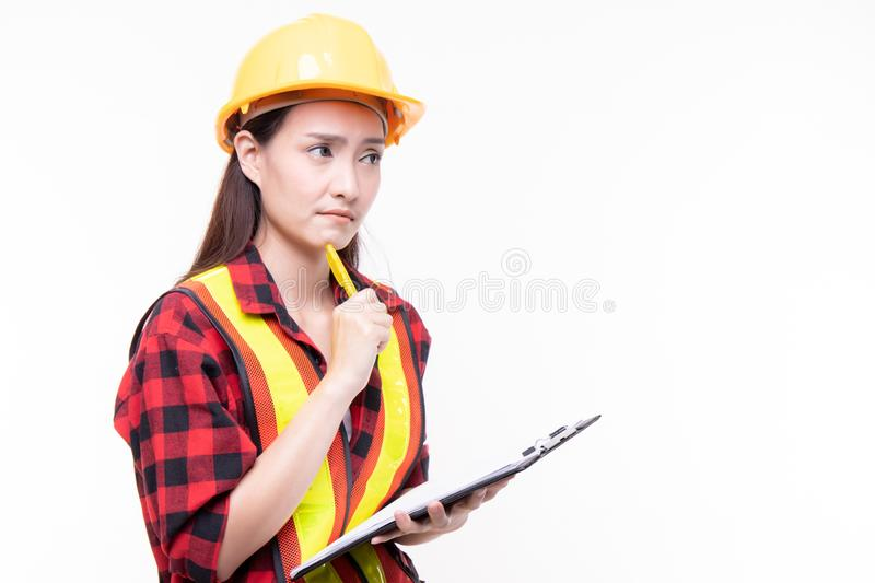 Attractive beautiful young asian construction female worker in yellow helmet and reflective vest holding clipboard isolated on stock photo