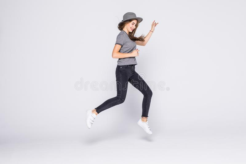 Attractive beautiful young girl wearing casual flying in air isolated over grey background. Attractive young girl wearing casual flying in air isolated over grey royalty free stock photography