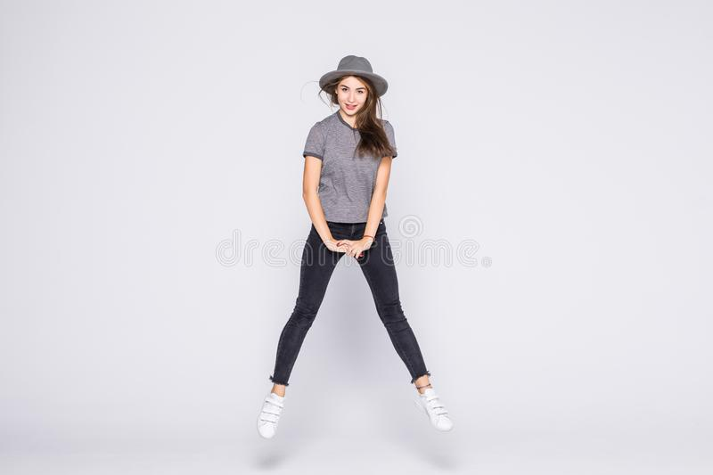 Attractive beautiful young girl wearing casual flying in air  over grey background. Attractive young girl wearing casual flying in air  over grey background stock photography