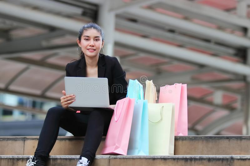 Attractive beauty young Asian woman with laptop and colorful shopping bags outdoors stock photos