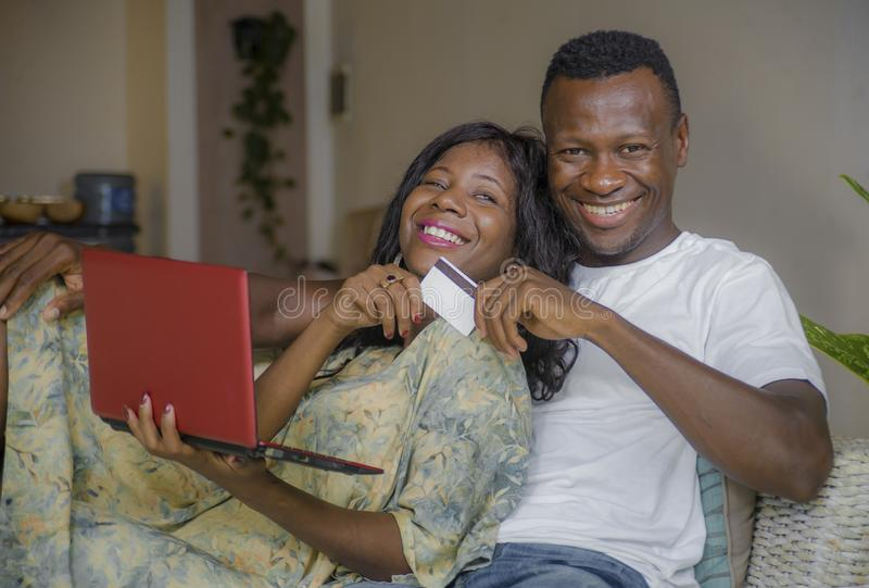 Attractive black African American couple at home sofa couch networking with laptop computer banking online or internet shopping. Young happy and attractive black royalty free stock images