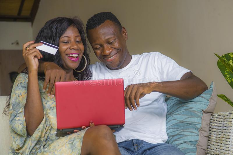 Attractive black African American couple together at home sofa couch networking with laptop computer banking online or internet. Young happy and attractive black royalty free stock photos