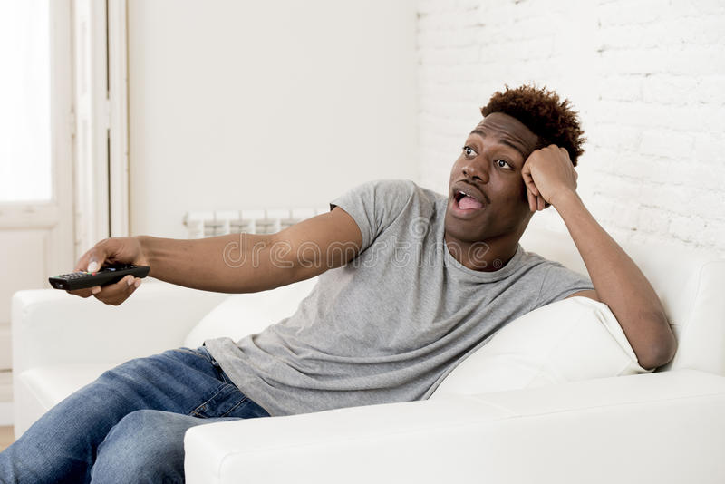 Attractive black african american man sitting at home sofa couch watching television stock photography