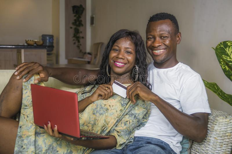 Attractive black afro American couple at home sofa couch networking with laptop computer banking online or internet shopping. Young happy and attractive black royalty free stock photography