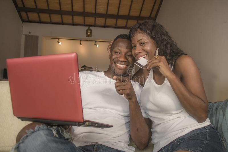 Attractive black afro American couple together at home sofa couch networking with laptop computer banking online or internet. Young happy and attractive black royalty free stock image