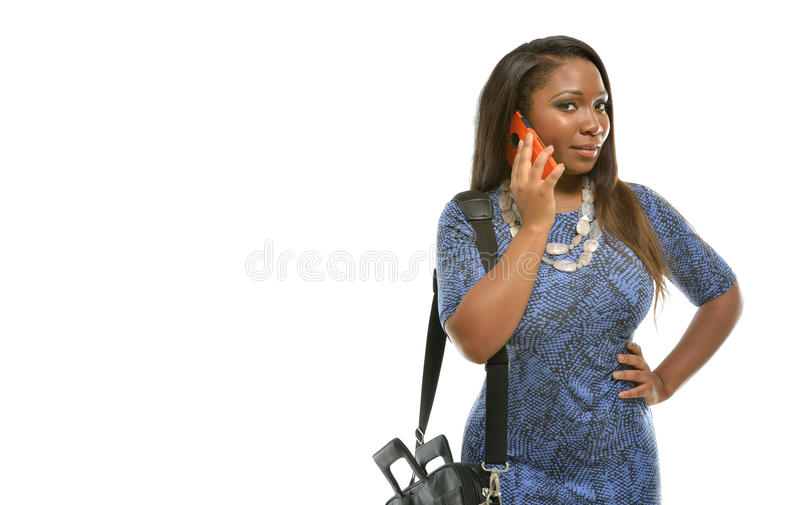 Attractive black business woman talks on phone. Beautiful African-American business woman in blue dress and in studio - carrying briefcase and talking on phone royalty free stock photo