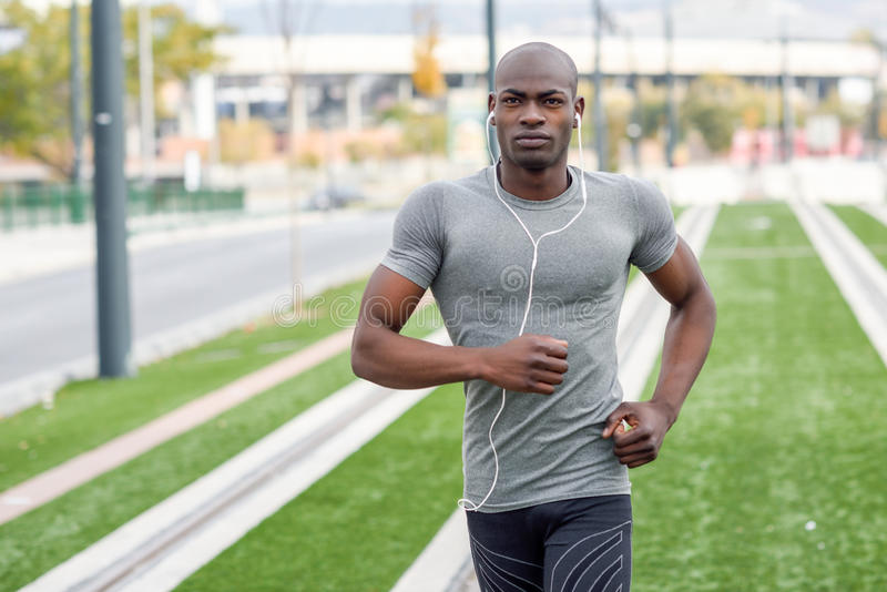 Attractive black man running in urban background. Black man running and listening to music in urban background. Handsome male doing workout outdoors stock photo