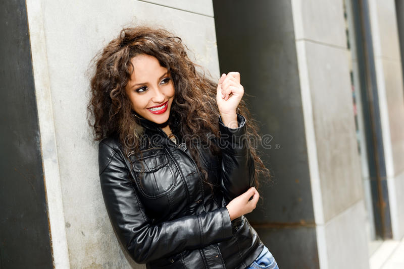 Attractive black woman in urban background wearing leather jacket. Portrait of attractive black woman in urban background wearing leather jacket royalty free stock photography
