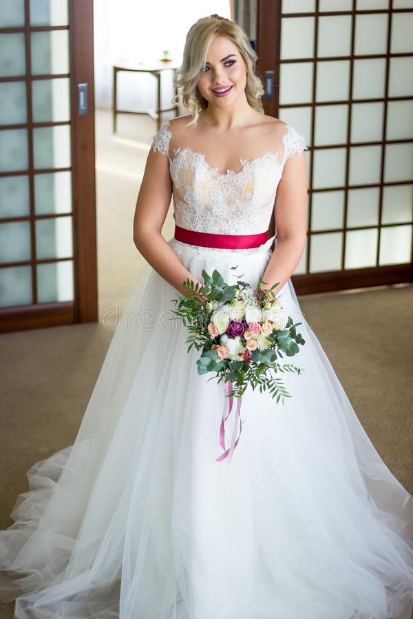 Attractive blond bride with huge bouquet of roses and peonies looks into the camera.  stock photo