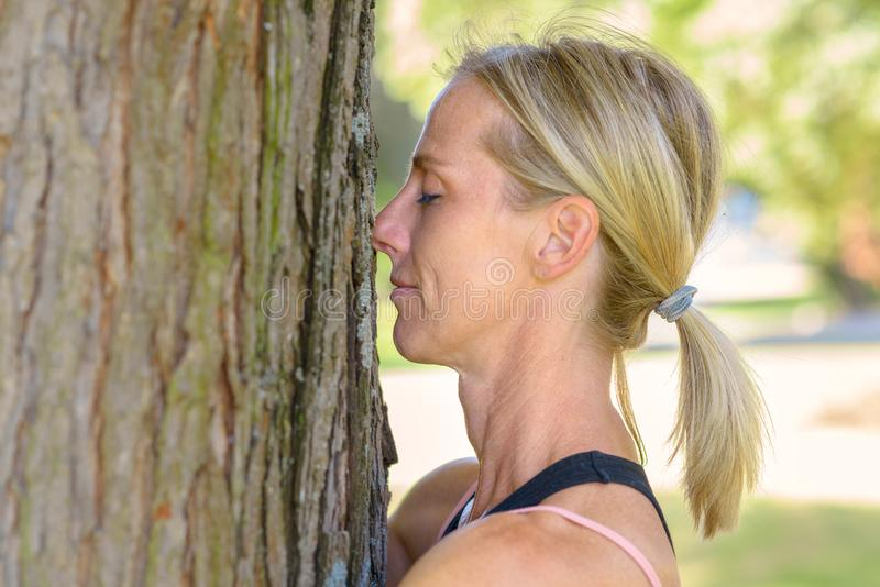 Attractive blond female nature lover hugging tree stock photography