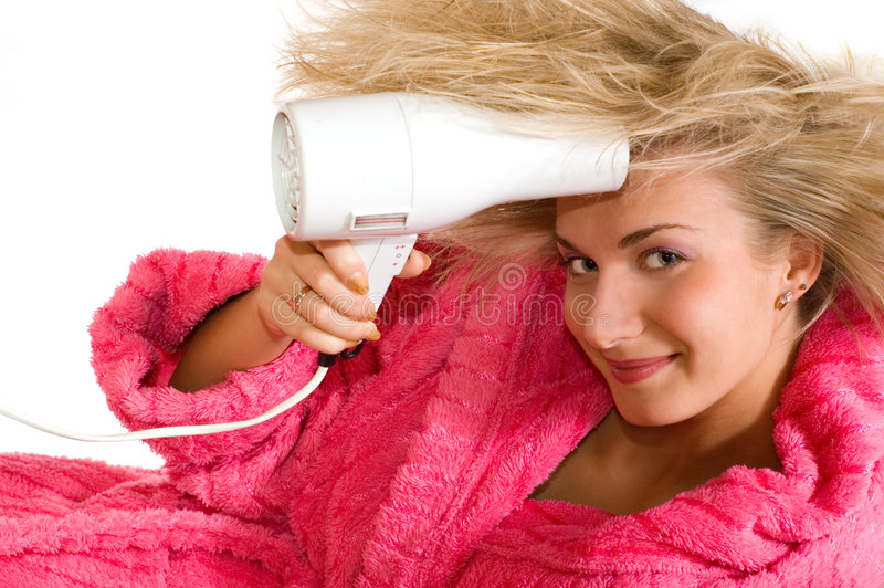 Attractive blond girl with a drier royalty free stock image