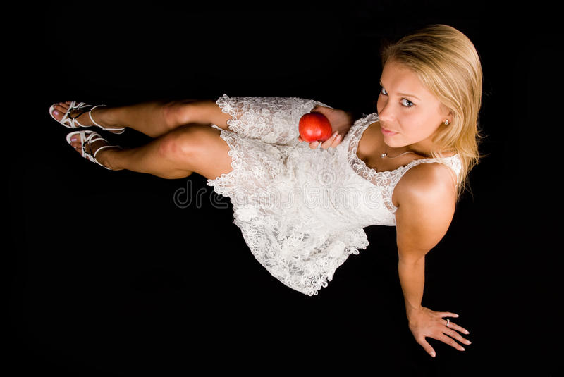 Attractive blond girl with red apple stock image