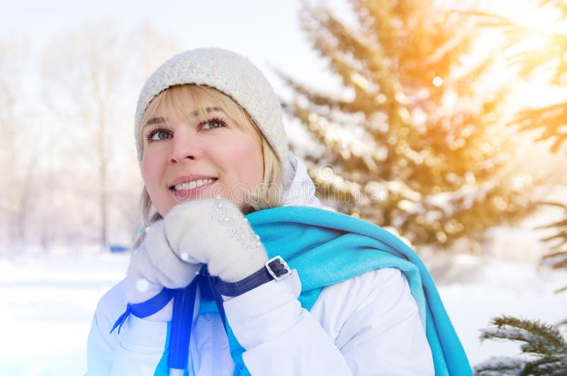 Attractive blond girl with a smile with ski poles in hands. During a short rest. pleasure from a walk on skis stock photo