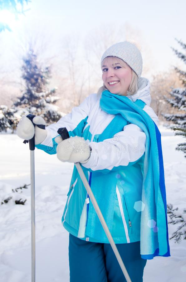 Attractive blond girl with a smile with ski poles in hands. Vertical view royalty free stock image