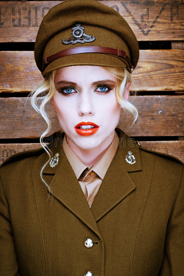 Attractive blond model in army uniform. Attractive blond fashion model wearing makeup with her hair curled in ringlets in a brown army uniform and peaked cap stock photography