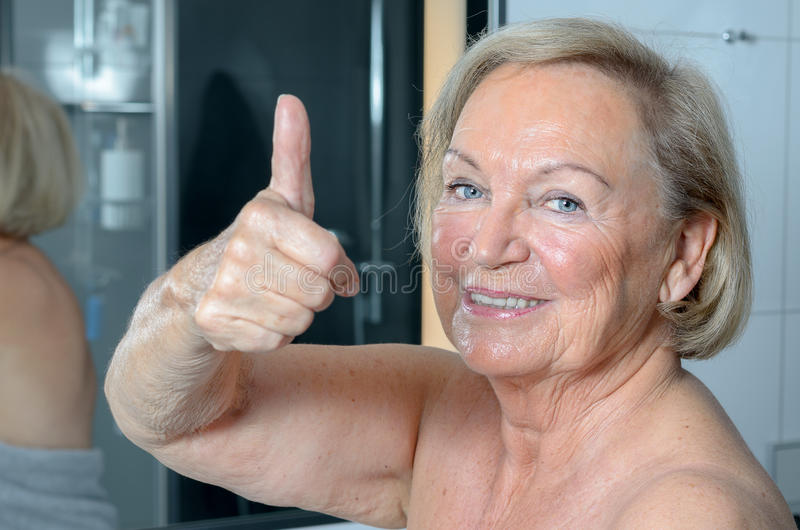 Attractive blond senior woman in a bathroom royalty free stock images