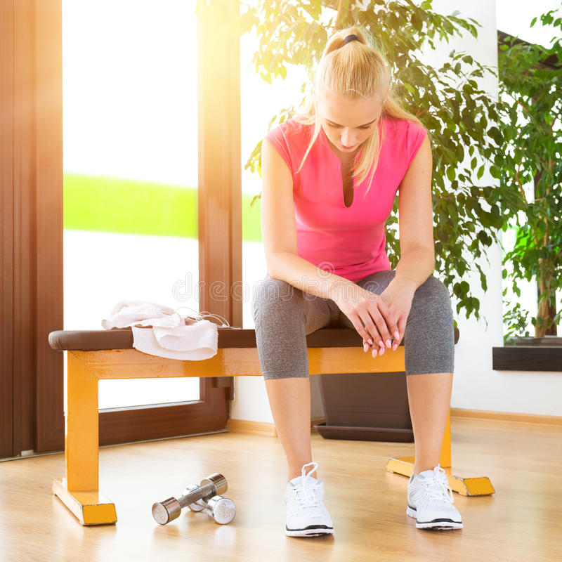 Attractive blond woman exhausted, resting after gym workout stock photo