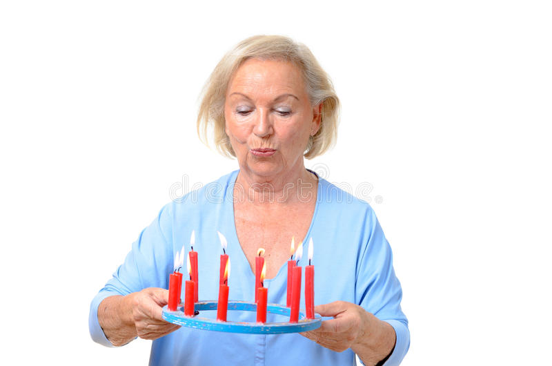 Attractive blond woman holding burning candles stock photo