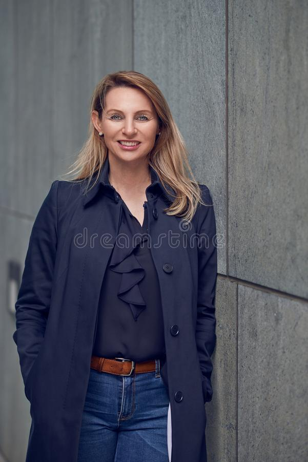 Attractive blond woman leaning against an urban concrete wall. Looking at the camera with a happy beaming smile with copy space alongside stock images