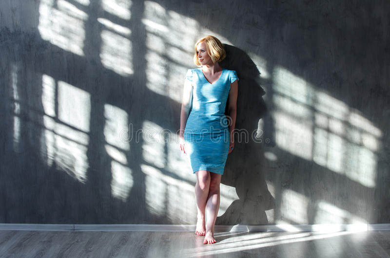 Attractive blond woman leaning on the wall and looking royalty free stock image