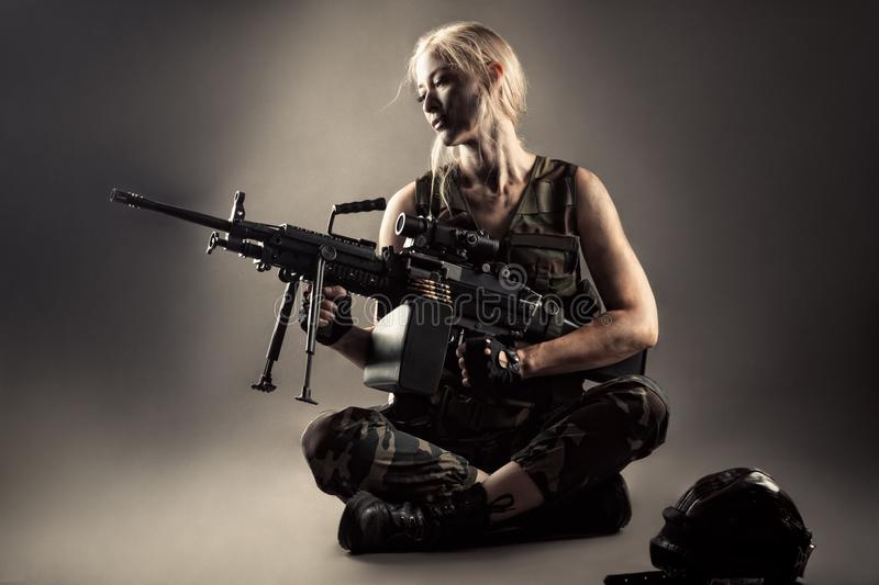 Attractive blond woman with machine gun in hands royalty free stock photo