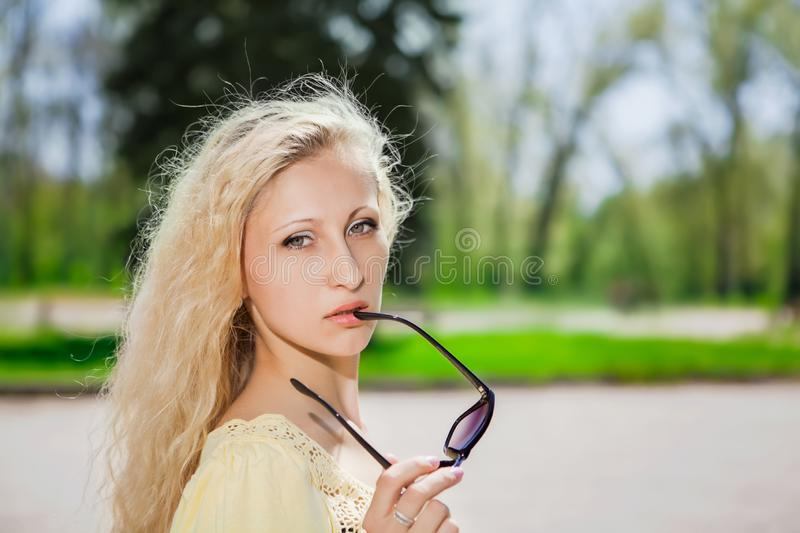 Attractive blond woman. Portrait of attractive blond woman posing with sunglasses in the park stock images