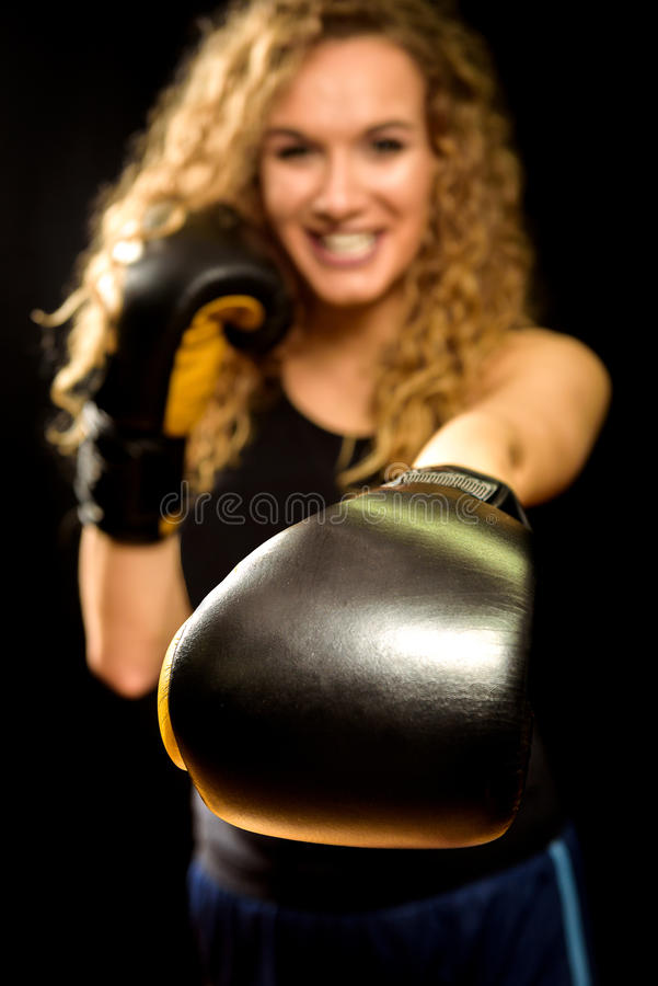 Attractive blond woman is punching with boxing glove. royalty free stock image
