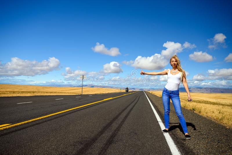 Attractive blond woman with red suitcase hitchhiking on an empty countryside road royalty free stock image