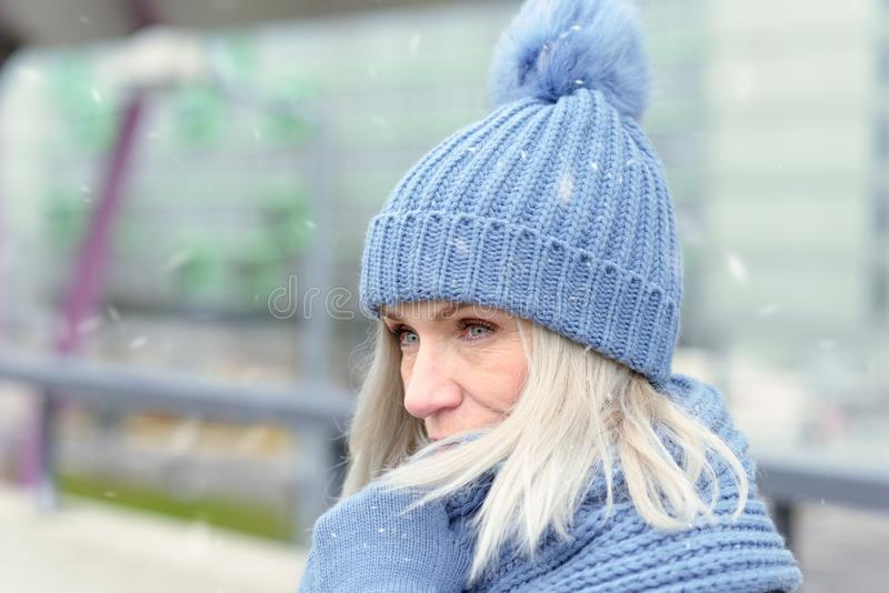Attractive blond woman snuggling into a warm scarf. Attractive blond woman in a trendy blue winter outfit snuggling into a warm scarf holding her gloved hands in stock photography