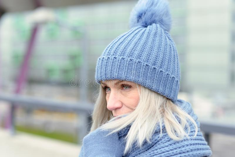 Attractive blond woman snuggling into a warm scarf. Attractive blond woman in a trendy blue winter outfit snuggling into a warm scarf holding her gloved hands to royalty free stock image