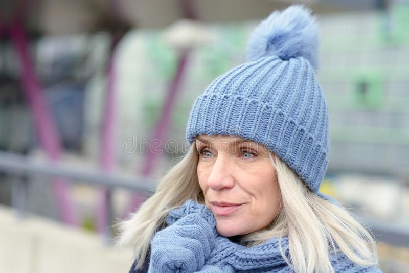 Attractive blond woman snuggling into a warm scarf. Attractive blond woman in a trendy blue winter outfit snuggling into a warm scarf holding her gloved hands to stock images