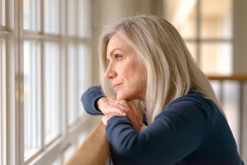 Attractive blond woman standing daydreaming. As she stands resting her arms and chin on a wooden bannister staring out of a large window stock image