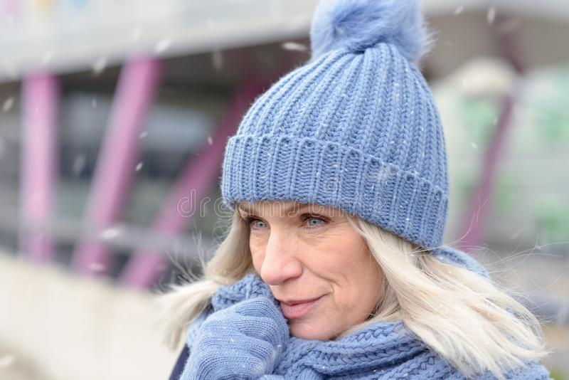 Attractive blond woman snuggling into a warm scarf. Attractive blond woman in a trendy blue winter outfit snuggling into a warm scarf holding her gloved hands in royalty free stock photos