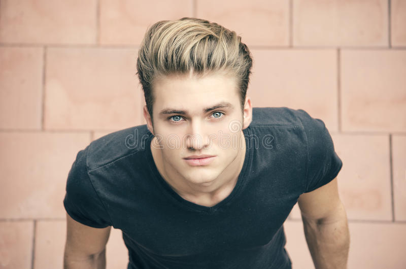 Attractive blond young man shot from above, looking up royalty free stock images