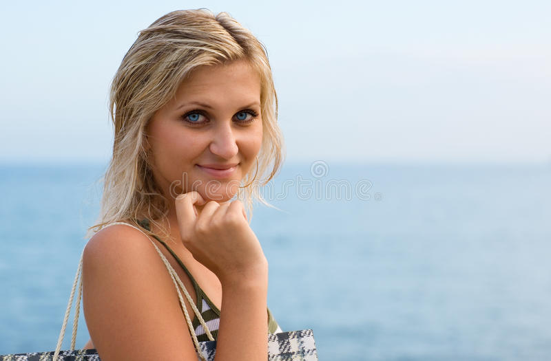 Attractive blonde in the blue sea. Evening stock images