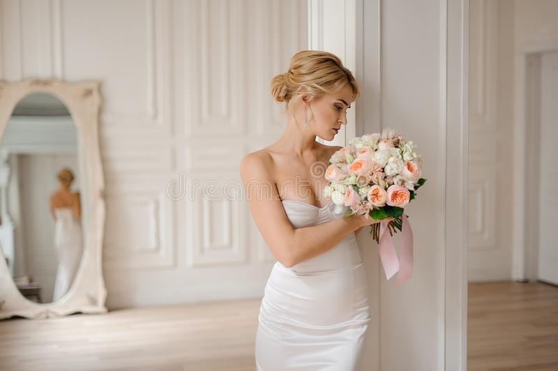 Attractive blonde bride in the elegant white dress holding a wedding bouquet stock images