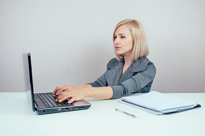 Attractive blonde businesswoman in a stylish business suit working in the office with a laptop. concept of business and royalty free stock photography