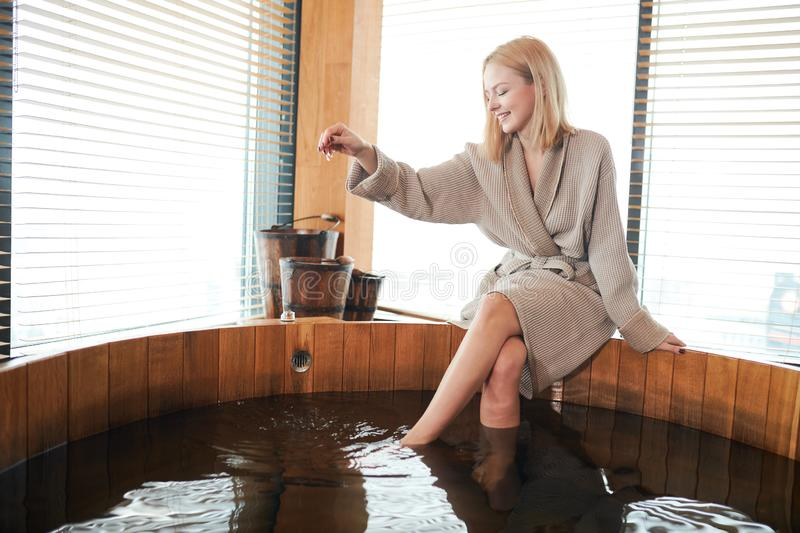 Woman relaxing near wooden barrel bath with glass in spa and sauna concept. Attractive blonde caucasian woman in bathrobe relaxing near wooden barrel bath in spa royalty free stock image