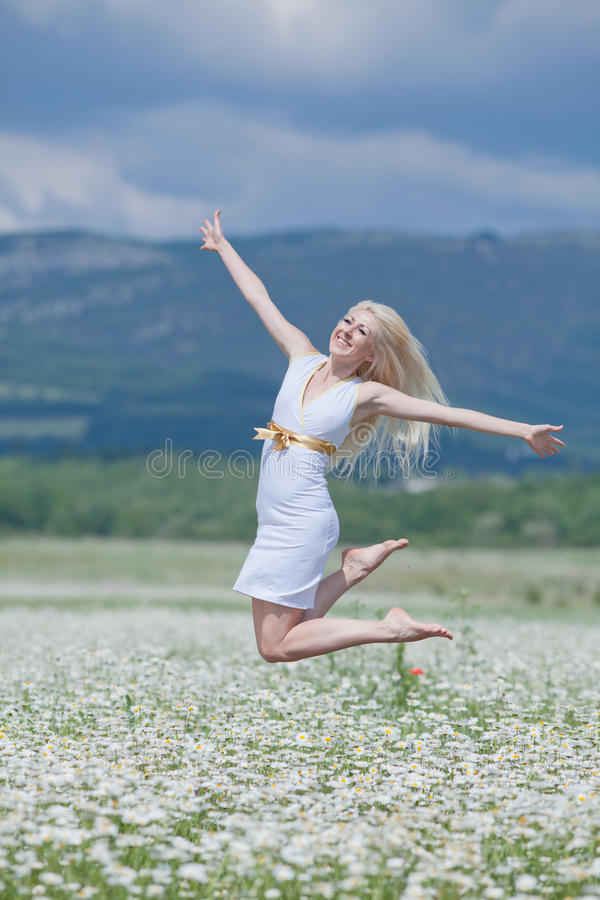 Attractive blonde in chamomile field. Young woman jumping high in wide chamomile field stock images