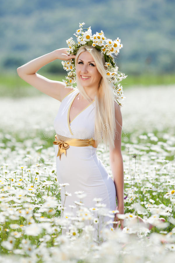 Attractive blonde in chamomile field. Young woman in wreath surrounded by chamomiles royalty free stock image