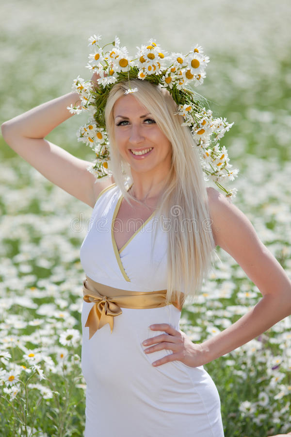 Attractive blonde in chamomile field. Young woman in wreath in chamomile field royalty free stock images